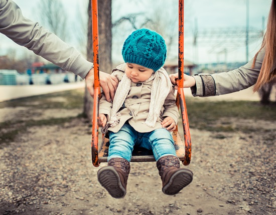 Child on a swing, inbetween her divorced parents