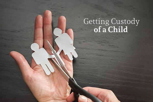 """A person holds a paper cutout of three people with a pair of scissors about to cut one of the """"parent"""" people cutouts from the other two beside the words """"Getting Custody of a Child"""""""
